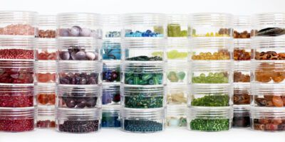 Multicolored glass beads sorted by color, organized in plastic containers