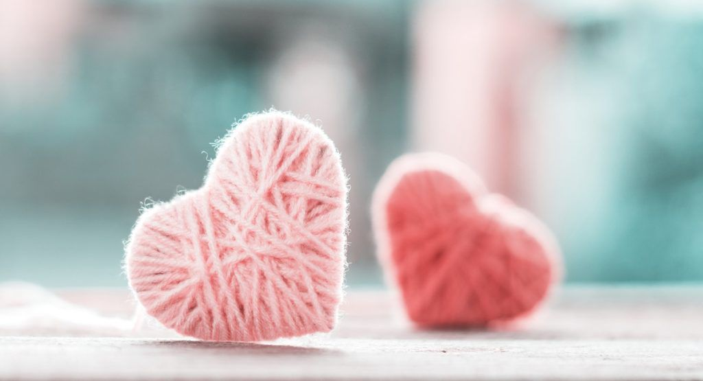 crochet Valentine's Day soft color knitting wool in shape of heart on vintage wooden with bokeh soft light background