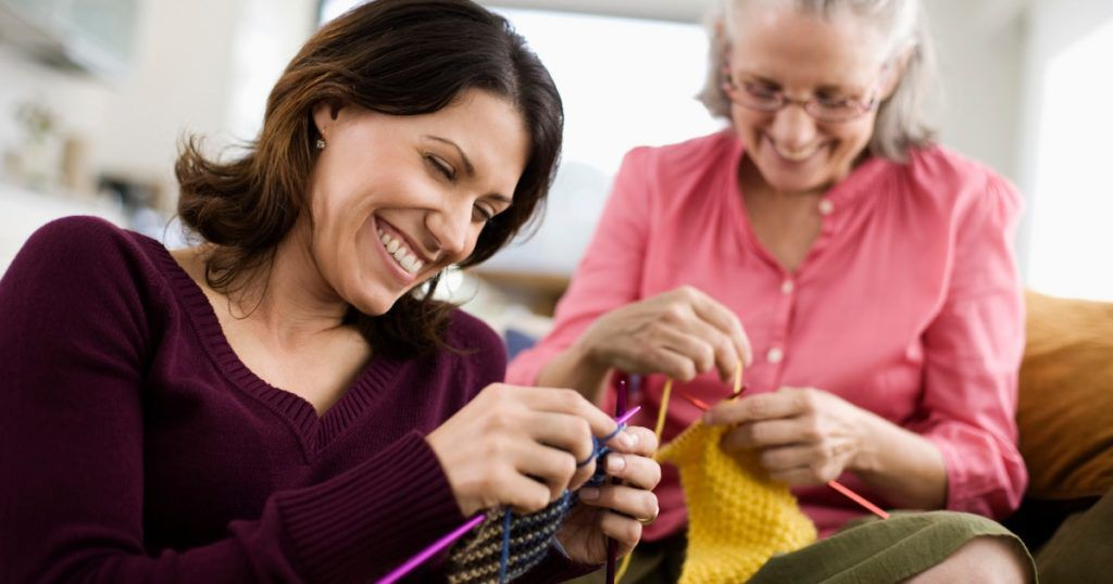 Two women teaching and learning to knit