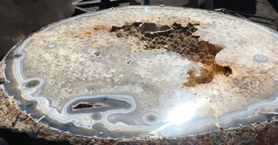 Tucson gem shows - If the slice is big enough, agate is durable enough to be used as a tabletop. Those pieces don't come cheap, but there tons of agate cabochons that make excellent jewelry and won't set you back much — or scare the heck out of you when you try to set one; agate table outside a Pueblo show tent at Tucson 2020; photo: M. White