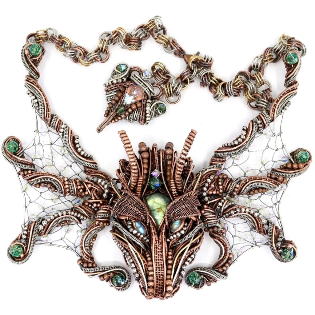 """Dragon of Mordiford, set, 6"""" x 3"""" dragon and wings; 6""""x 10"""" with chain, copper, fine silver, brass, gold-filled and Argentium Sterling wire, silver and copper beads, labradorite, rainbow moonstone, Swarovski crystal, wire weaving, coiling, chain making. Head attached to wings with latch system and can be worn separately; earrings and tail on extension chain; photo: Debbie Benninger"""