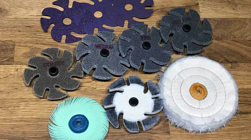 Back, left to right: Purple ceramic abrasives, 80, 120, and 220-grit; Center: scratch eraser set; Front, left to right: radial polishing brush (1 micron, green), felt buffing disc, and buffing wheel